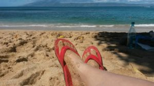 Two feet in red sandals on a sandy beach, with ocean waves about 50 yards away, and the sun is shining.