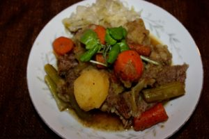 Shallow china bowl with beef stew meat, carrot, celery, potato, and rice arranged in the center.