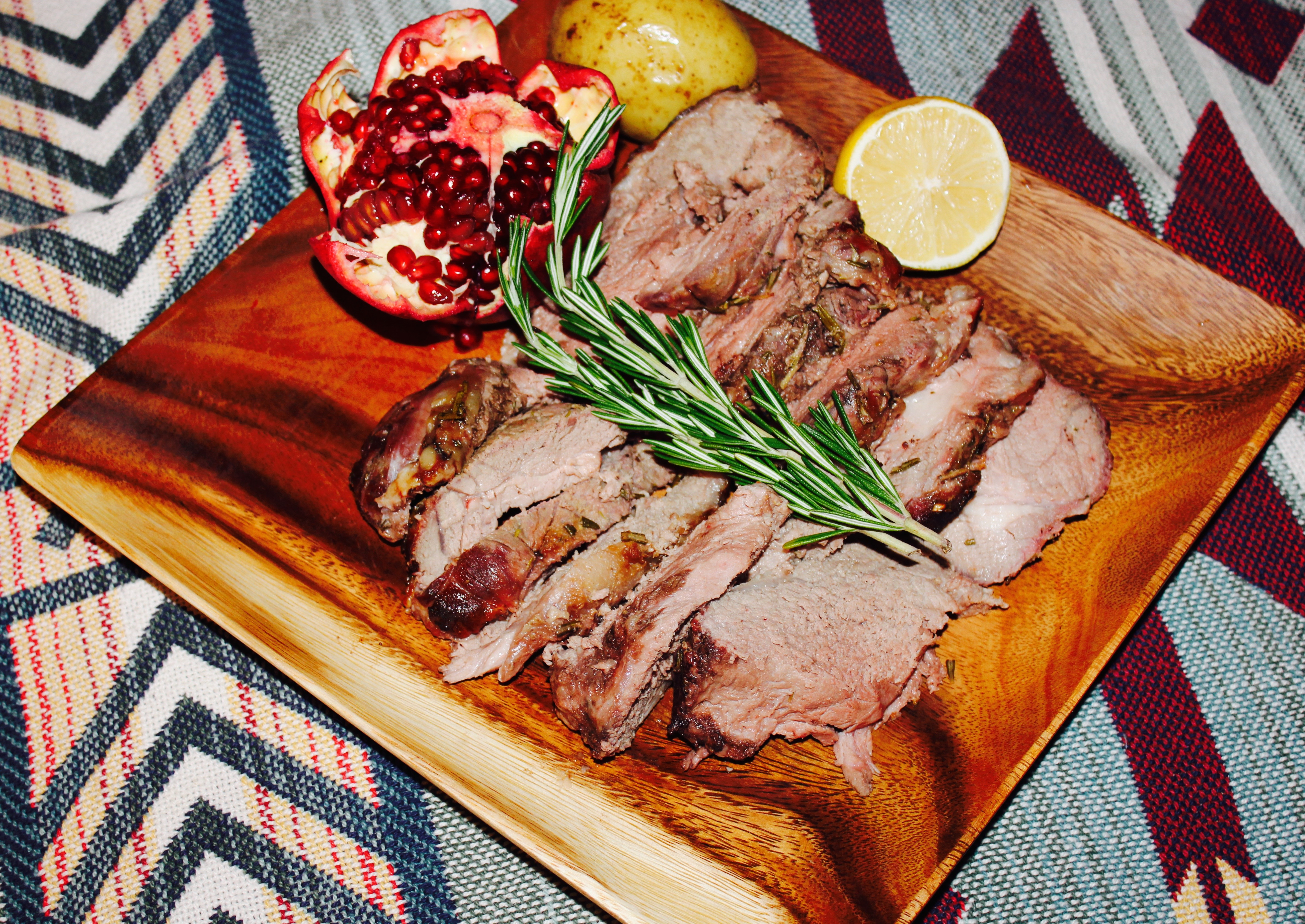 Leg of lamb cooked and sliced onto a wood plate, with a pomegranate opened, one large Yukon gold potato, a half lemon, and two stalks of Rosemary laid across the sliced lamb.