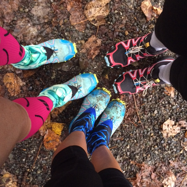 Three sets of feet and legs in bright colored trail shoes, standing on dirt and leaves. Photo by Imei.