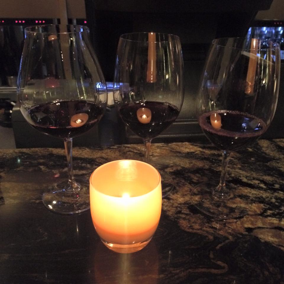 Three tall wine glasses with a pour of red wine in each, yellow glowing candle in front of wine glasses casts a reflective glow off each glass. Photo by Imei.