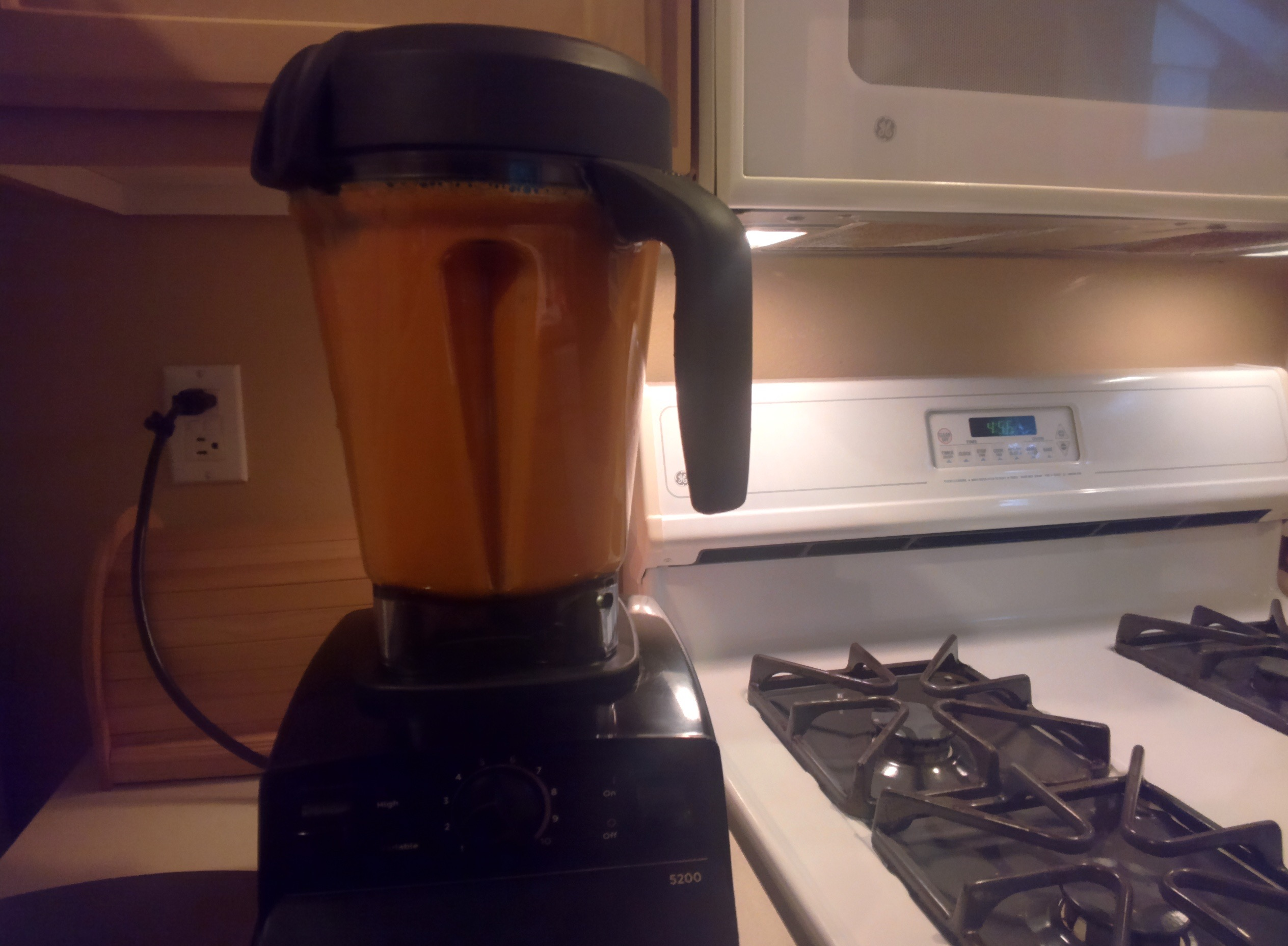 Blender with black cap and base, filled with blended carrots and sweet potato, sitting on countertop next to stove.