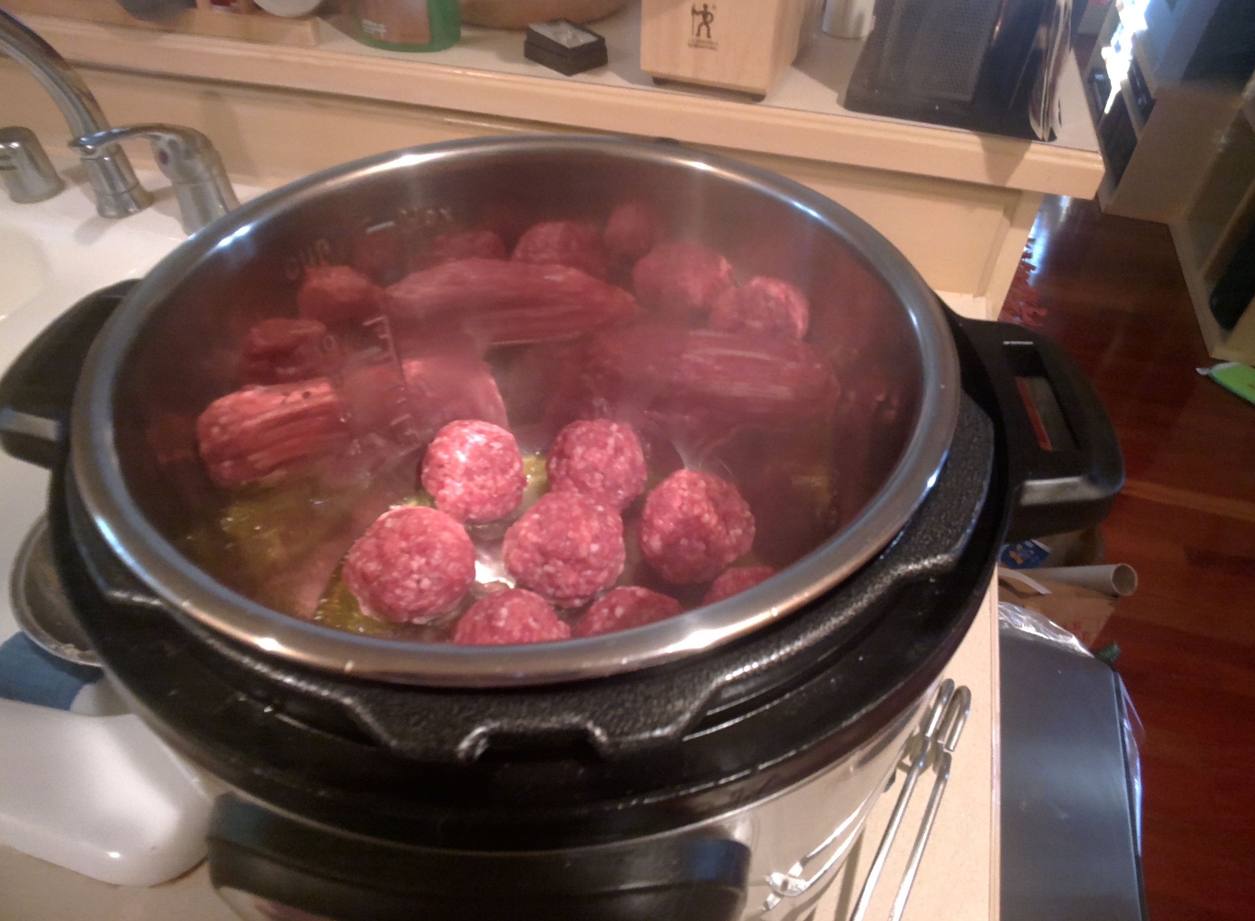 Lamb meatballs saute inside the InstantPot with the lid off.