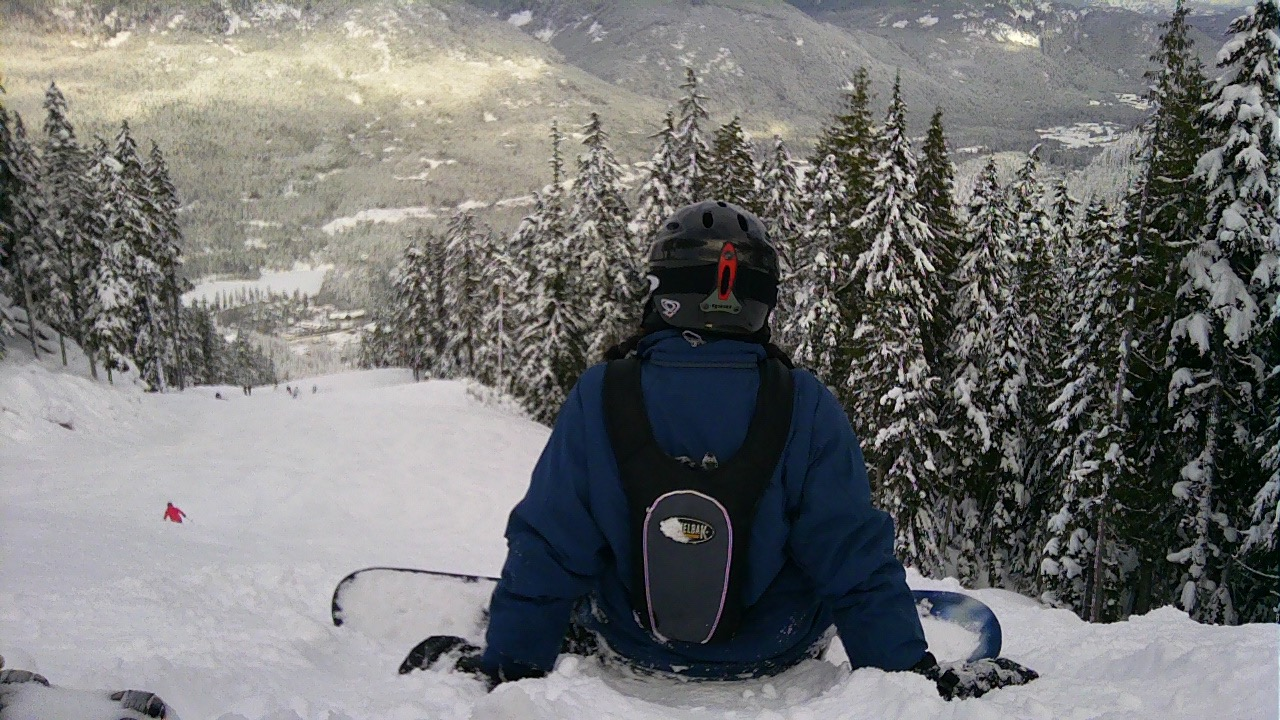 Female snowboarder wearing helmet, dark blue jacket, water backpack, sits in snow with snowboard on, looking downhill to Whistler Village below