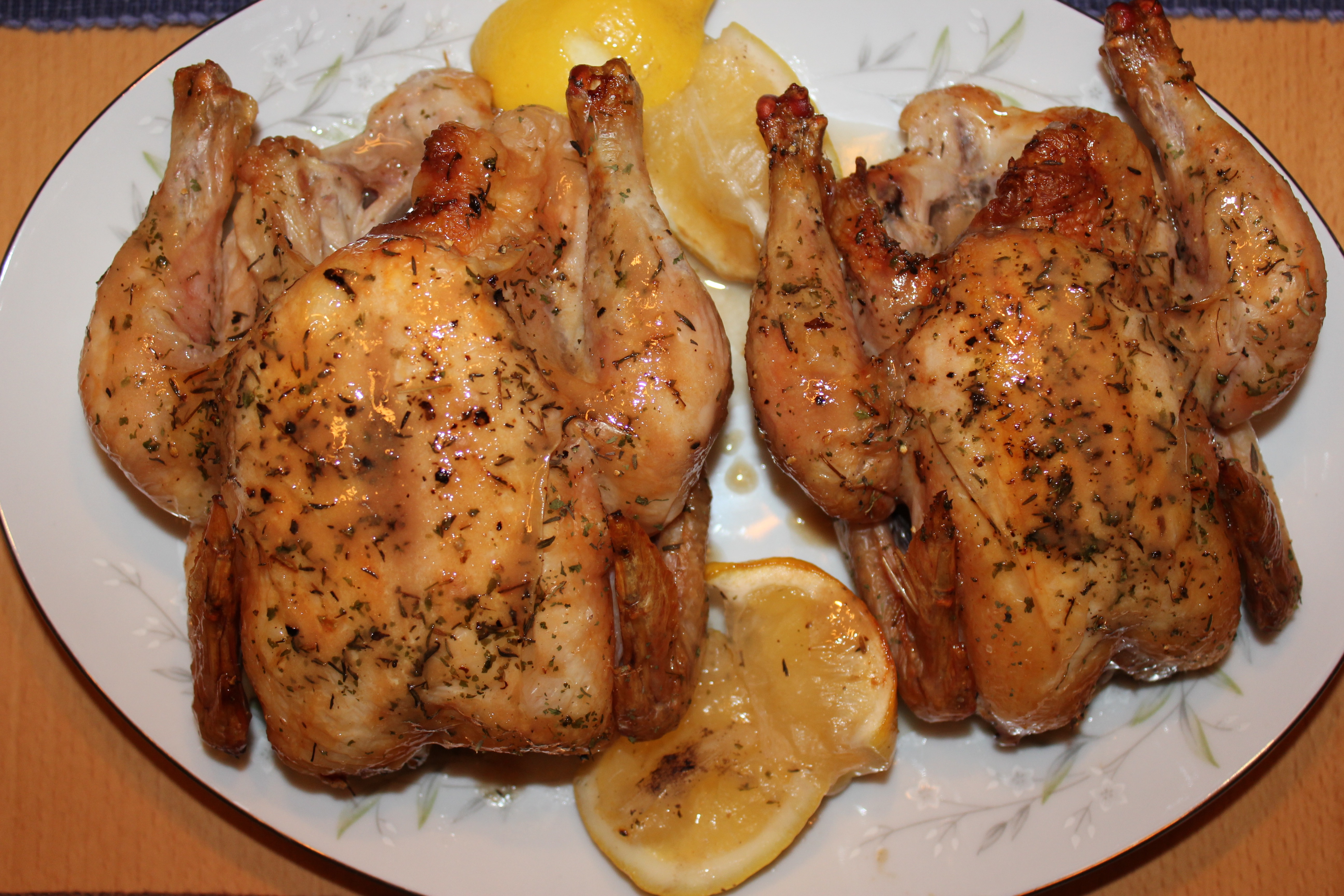 Two Cornish game hens, side by side, one a white china plate, with herbs on top and two lemon halves.