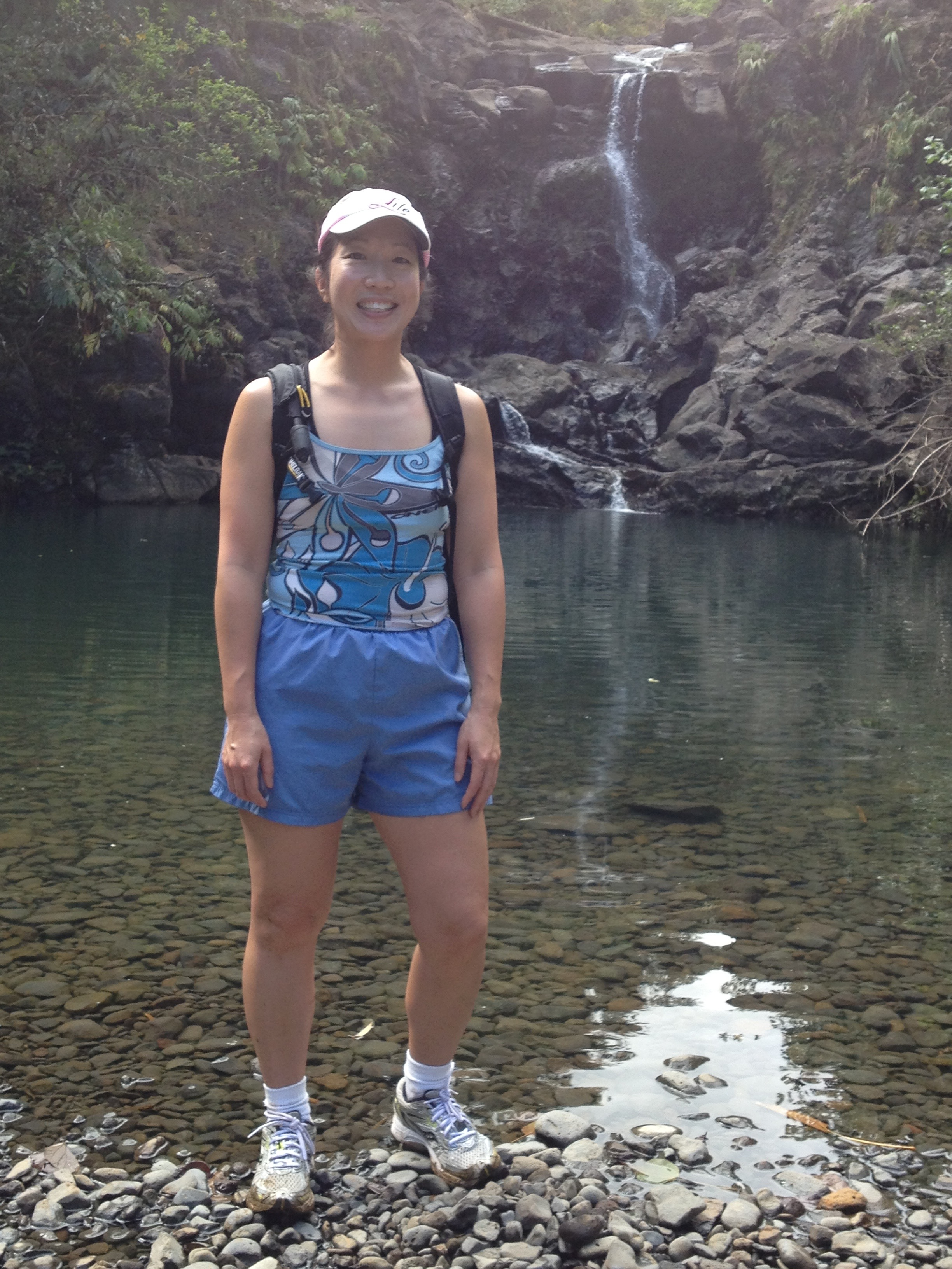 Author of post wearing shorts and a swim tank top, running shoes and socks, standing by a river in Maui, Hawaii.