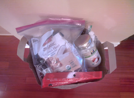 Top view of bag of dry goods, plastic freezer bags, coconut oil in a jar.