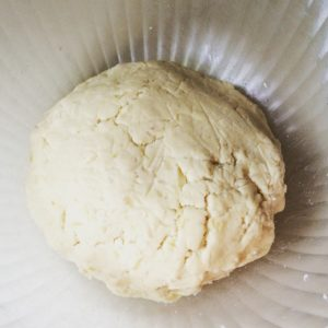 Clear bowl with dough ball in center, kneaded.