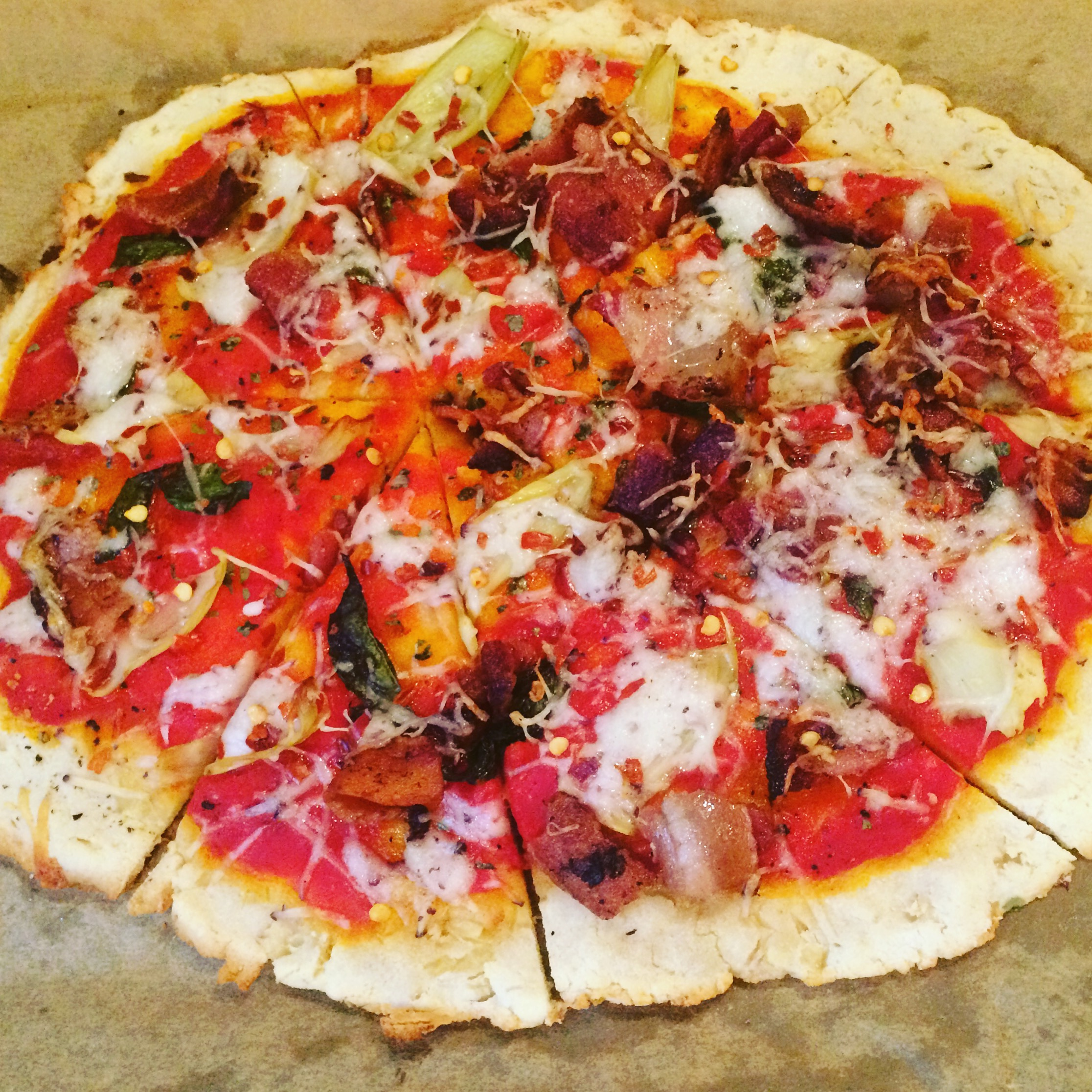 Pizza with toppings on a piece of parchment paper, edges of crust are browned.