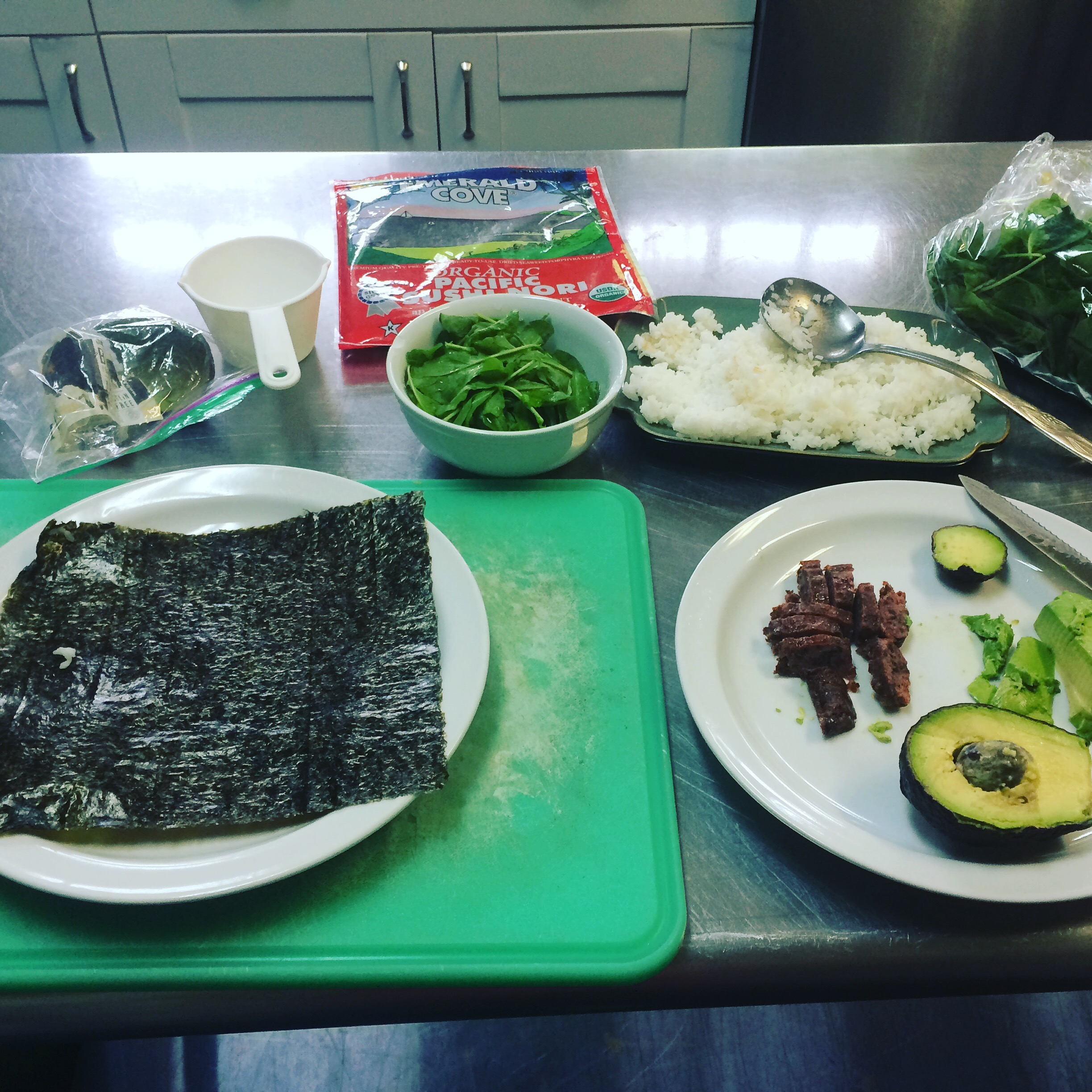 plate with seaweed, bowl with greens, white rice cooling on a plate, another plate with avocado halfves, and EPIC bar cut into smaller pieces, and a measuring cup.