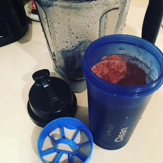 Vitamix pitcher, blue Clean Tek container with strainer insert and lid off to the left side.
