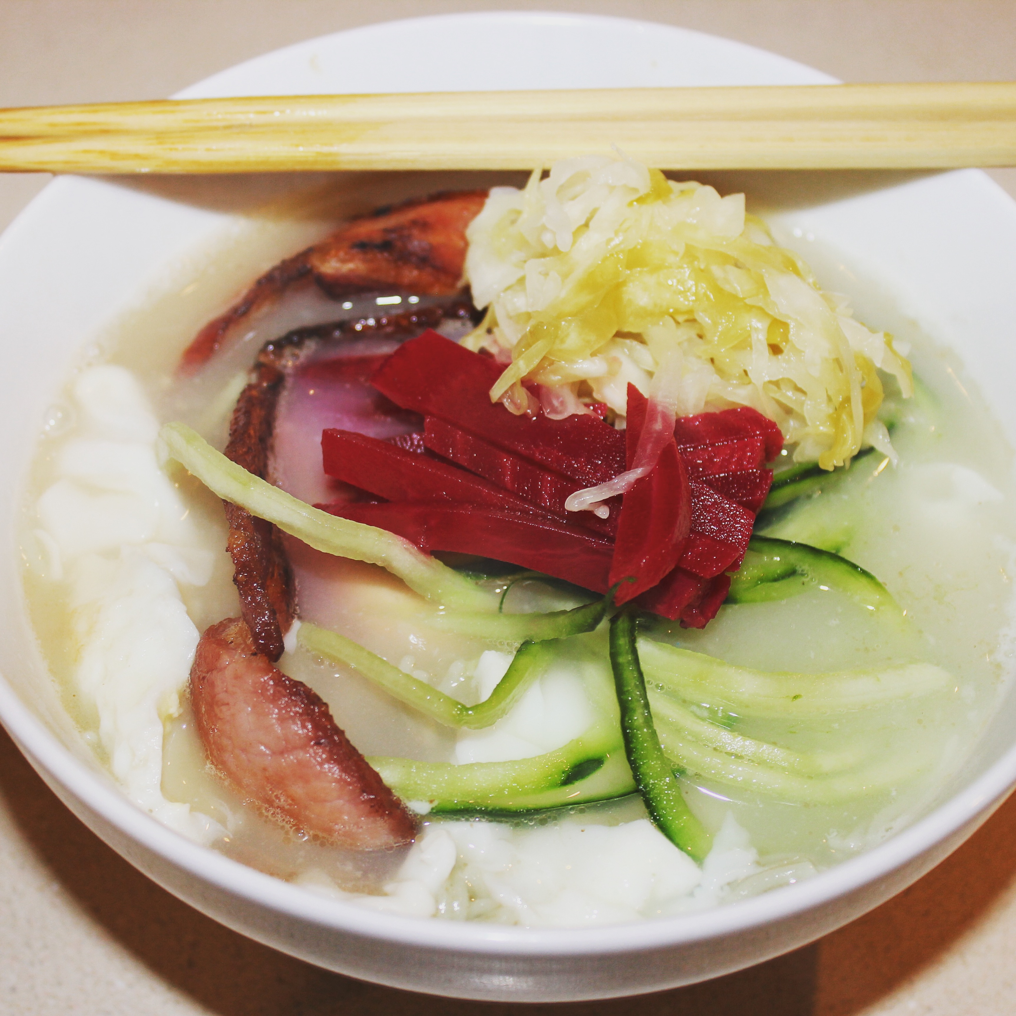 White bowl with noodles, vegetable, beets, bacon, and sauerkraut, with a pair of chopsticks across the top. Photo by Imei Hsu.