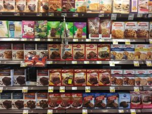 Cake mixes of a variety of brands on the supermarket shelves.