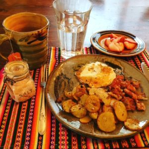 Plate of breakfast foods, fruit, coffee, and salt container sitting on a placemat on a wood table