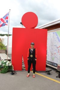 Author standing in front of Ironman M dot sculpture wearing ironman medal
