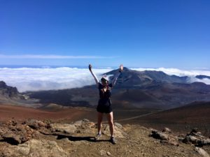 Author standing on the edge of the Haleakala Crater trail under blue skies.
