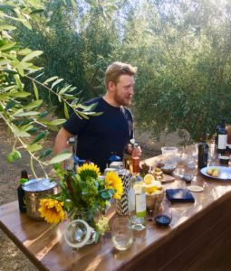 Chef with beard stands behind counter in the middle of an olive grove. Table has wine, steel drink container, flowers, and small plates of food.