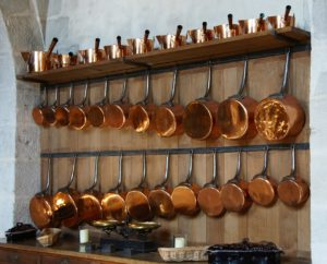 copper pans line a white wall above a wood countertop and cooking space in a commercial kitchen.