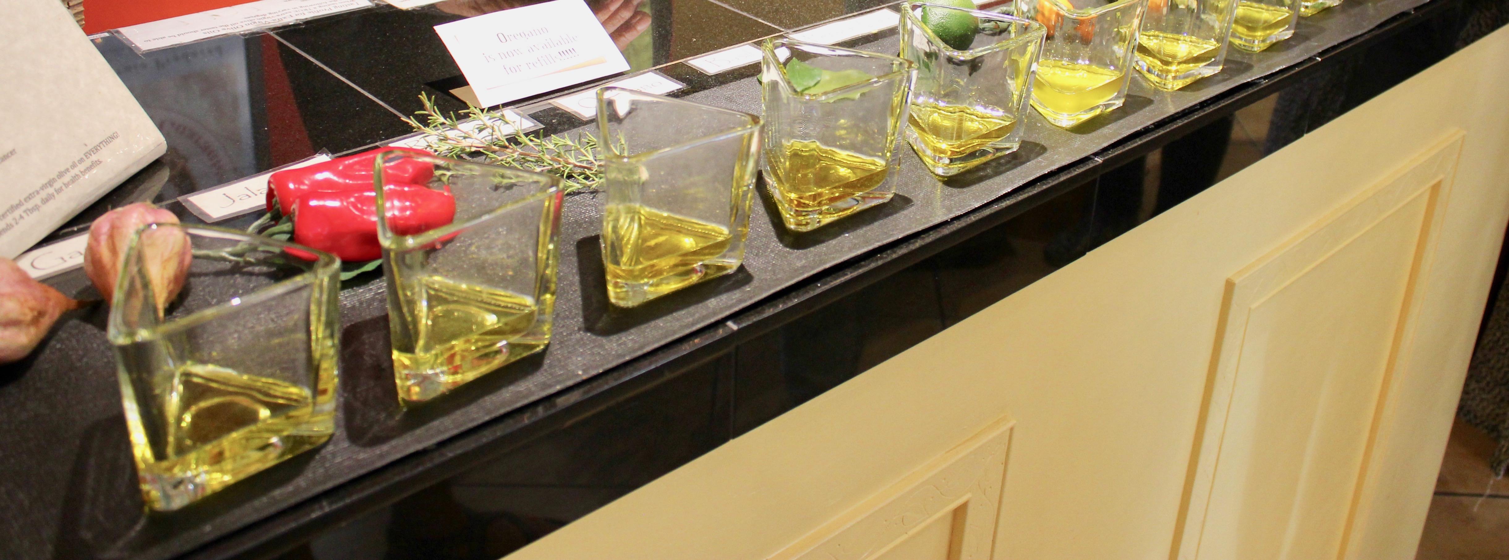 Triangular glasses with olive oil, herbs and spices, on a counter, ready for tastings.