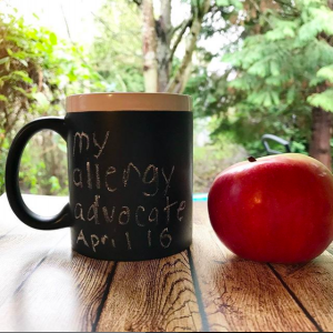 "Black mug with words, ""My Allergy Advocate April 16"" in chalk, apple next to cup, resting on a wood board, trees in the background of morning light"