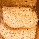 Slices of bread on top of a wooden board next to a loaf of bread, with a serrated bread knife.